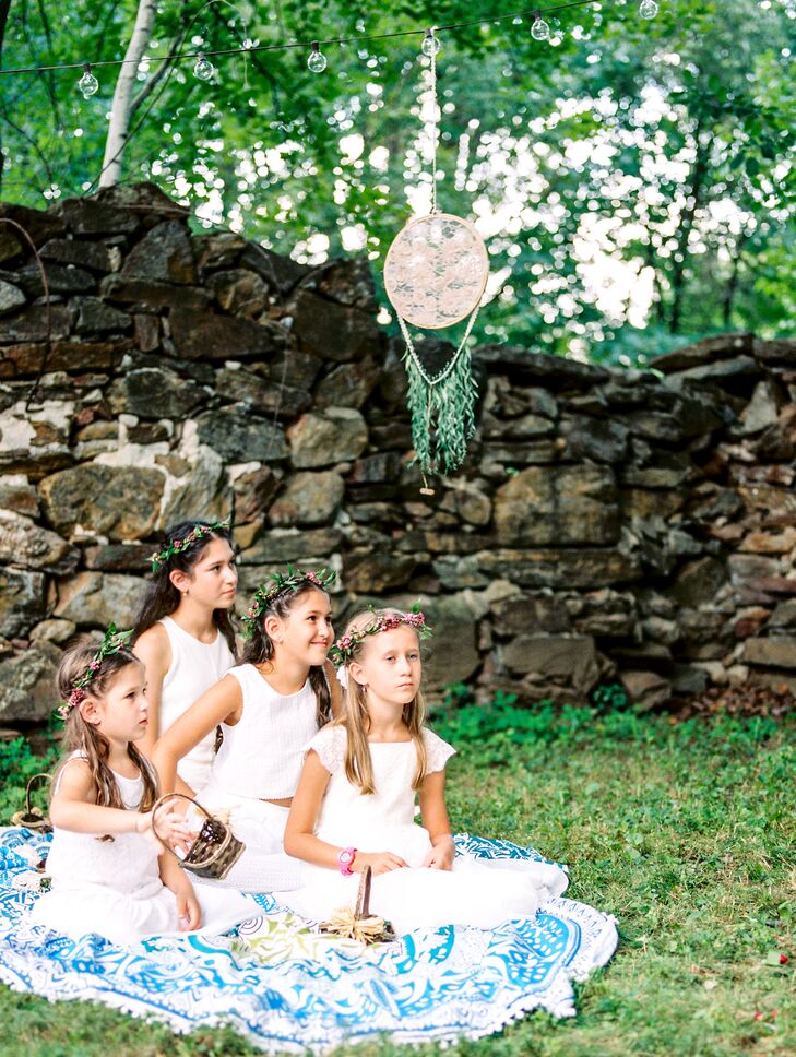 The younger members of Nicole's bridal party channeled the evening's bohemian feel, wearing white linen frocks, delicate flower crowns and their hair down in wavy locks. During the ceremony, the girls spread out on a colorful pom-pom trimmed blanket laid out beside the chuppah.rnThe younger members of Nicole's bridal party channeled the evening's bohemian feel, wearing white linen frocks, delicate flower crowns and their hair down in wavy locks. During the ceremony, the girls spread out on a colorful pom-pom-trimmed blanket laid out beside the chuppah, emphasizing the evening's carefree vibe.