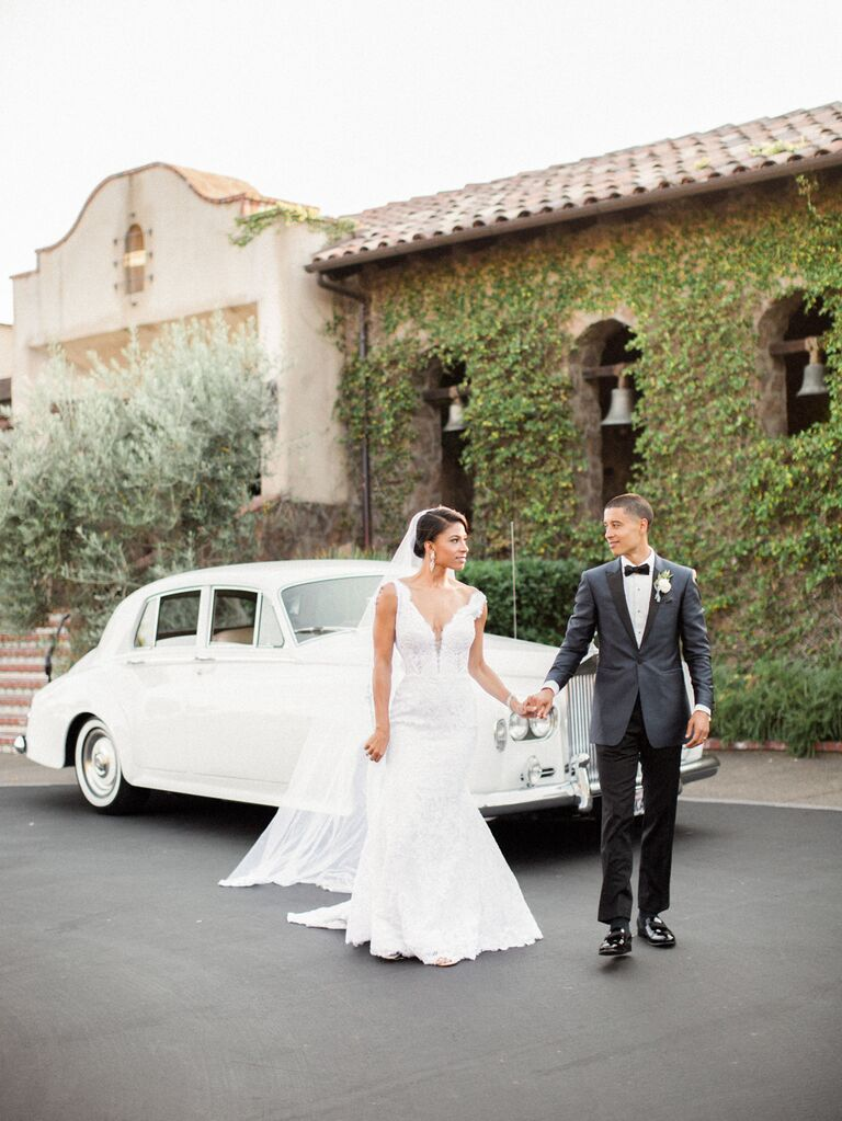 Bride and groom standing in front of getaway car