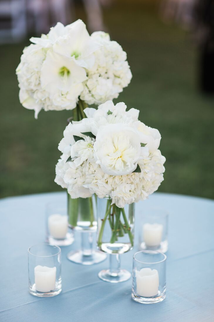 Simple glass vases were filled with white orchids, hydrangeas, and roses. Tea candles