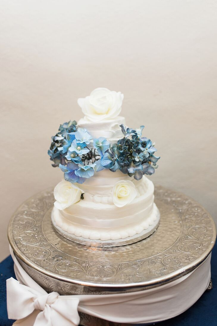 For dessert, Chelsea and Clay enjoyed a three-tier white buttercream wedding cake. The cake was topped with white roses and blue hydrangeas to match the palette.