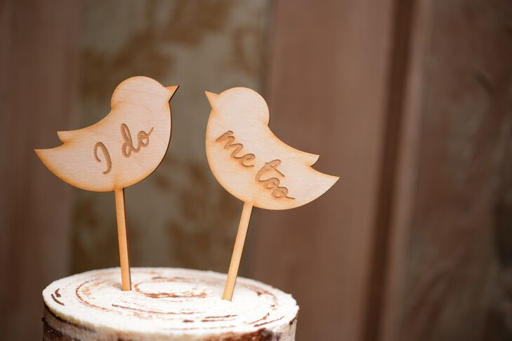"""On top of the couple's rustic cake were a pair of wooden birds branded with the words, """"I do"""" and """"Me too."""""""