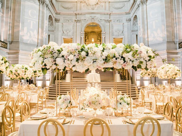 Lavish regency-inspired wedding reception with towering floral centerpieces and gold chairs