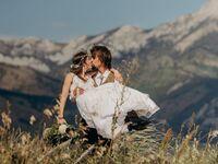 wedding couple kissing with montana mountain backdrop