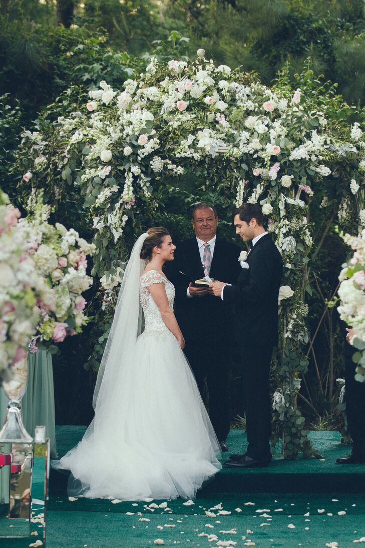 Ashley and Freddy exchanged their vows under a lush arbor of ivory roses, snapdragons and greenery. Their ceremony took place in Ashley's parents' backyard.