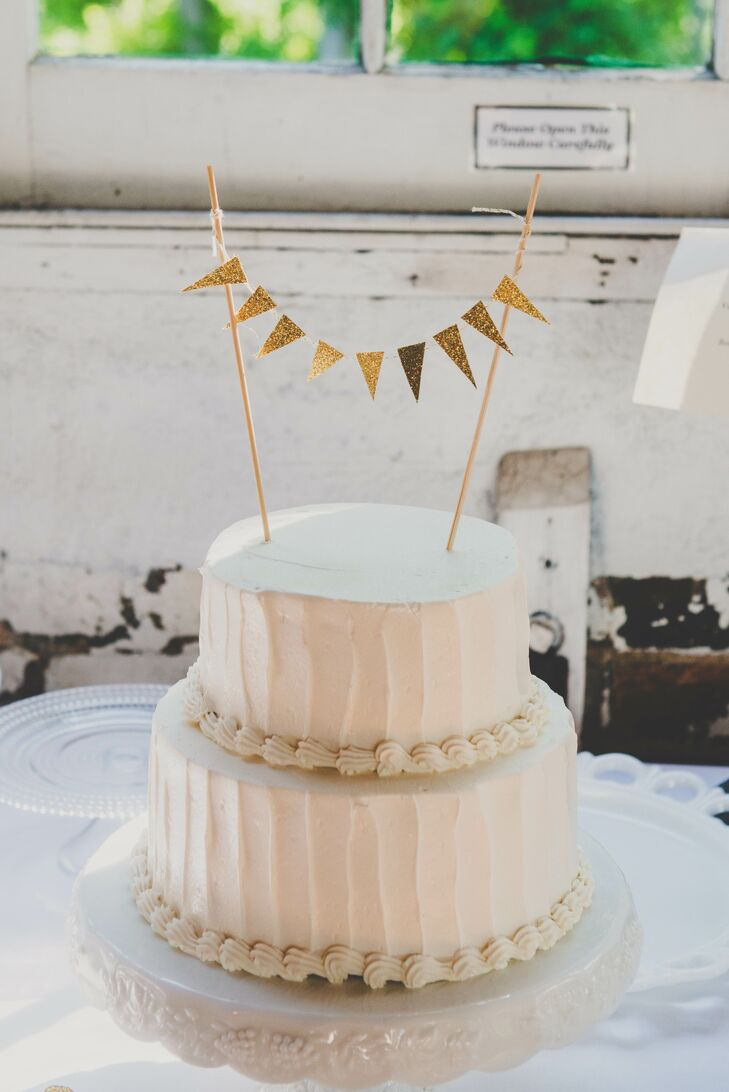 The two-tier ivory wedding cake was covered in buttercream and had vanilla-flavored cake. The bottom of each tier was bordered with thick texture, and the top was accented with a DIY gold flag topper.