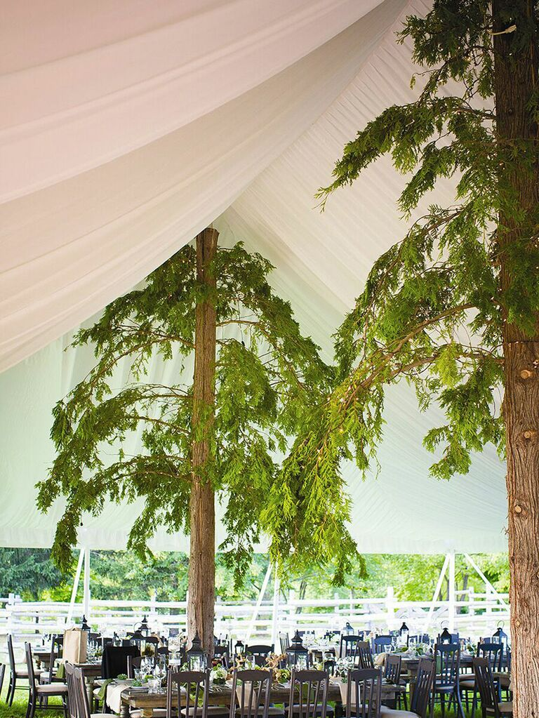 Tree-inspired wedding tent pole covers with thick green leaves