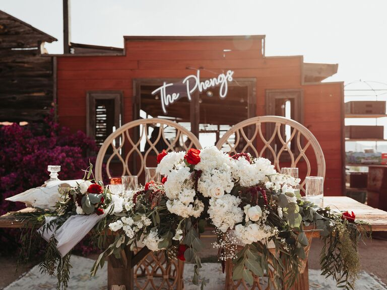 Bohemian wedding sweetheart table with red and white flowers and custom neon sign