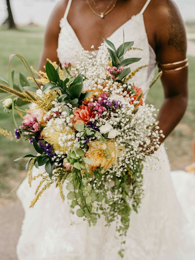 Bride holding bouquet of wild flowers and baby's breath for summer wedding