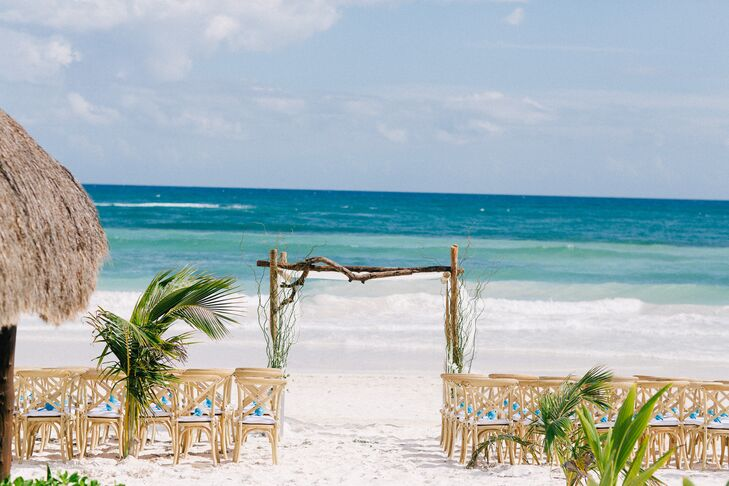 Danielle and Jason had a traditional Jewish ceremony on the beach underneath a driftwood chuppah at Akiin Beach Club in Tulum, Mexico. Light wooden furniture with turquoise accents and greenery created a rustic, natural atmosphere.