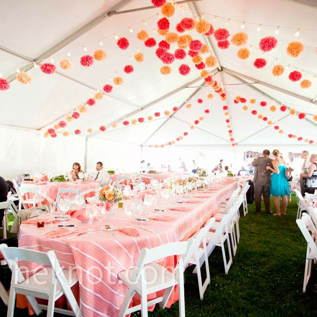 Tissue paper pom-poms and strands of bulb lights hung from the tent's ceiling. The bridal party, plus their dates, sat at a long banquet table in the center.