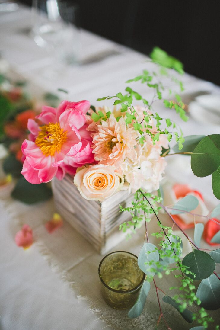 Weathered wooden vases were filled with arrangements of peach dahlias, roses and stock and vibrant pink peonies and cascading greenery, adding a fresh, whimsical touch to the reception tables.