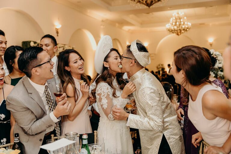 Couple eating food together during Vietnamese wedding reception