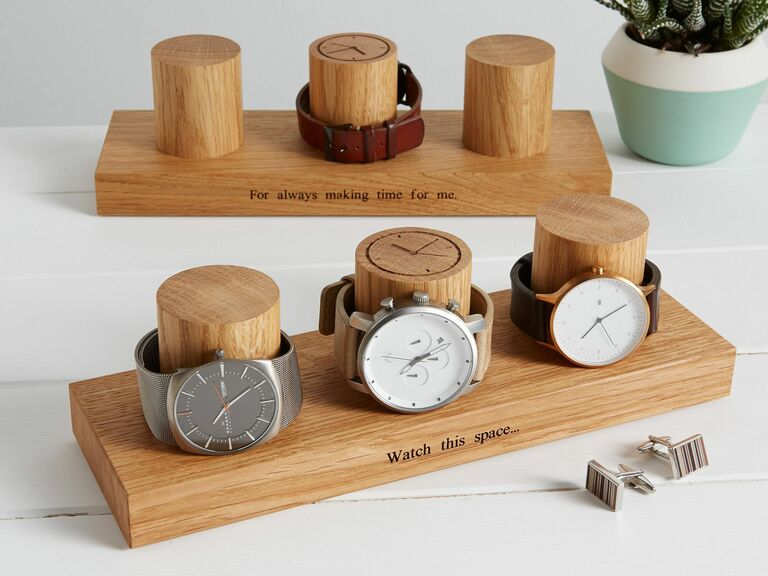 Two wooden watch display stands engraved with cute puns