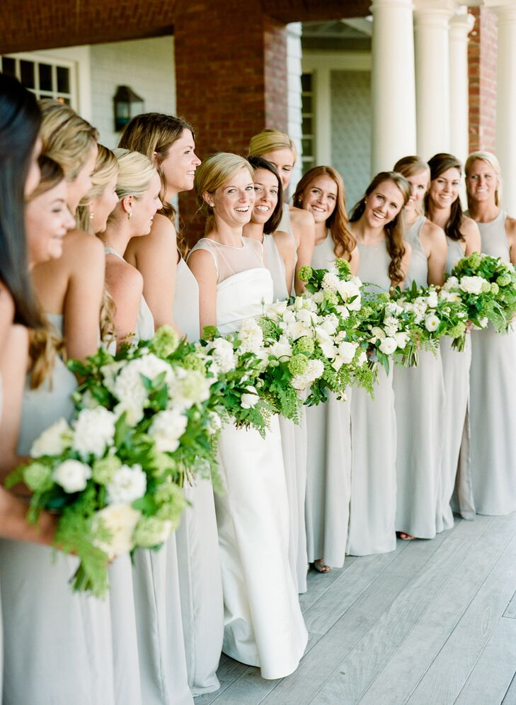 """Caroline's lucky 13 bridesmaids donned high-neck Natalie Deayala gowns in dove gray to match the white florals and greenery. """"When picking out the dress, I knew I wanted something simple and not too formal, since it was an outdoor wedding,"""" Caroline says."""