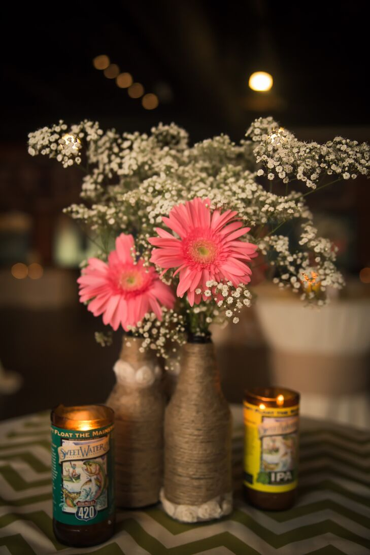 Bunches of bright pink gerbera daisies, hydrangeas and baby's breath filled rustic twine, pearl and lace-wrapped bottles  and mason jars that Sarah had made herself.