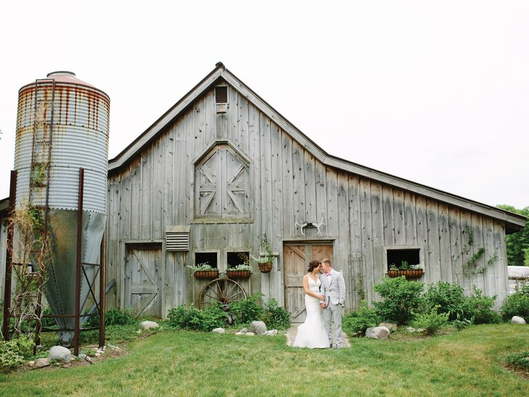 Bride And Groom Stand In Front Of A Barn On Their Wedding Day