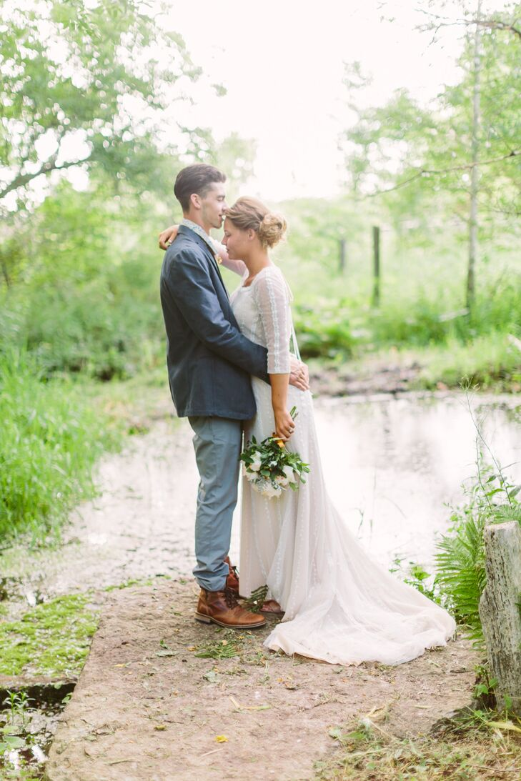 The bottom of Megan's ivory wedding dress train bundled behind her as she faced Carson. She wore a classic gown that blended in with the environment's natural colors.