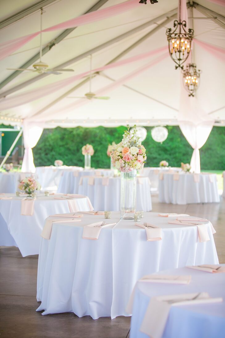 The waterfront reception took place under a large white tent with blush-colored fabric draping from the top with hanging lanterns. White linen tablecloths with blush napkins and flowers were placed on the dining tables.