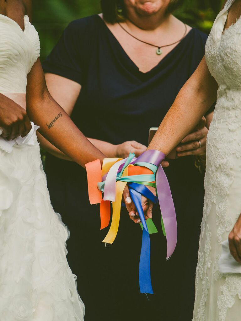 Brides holding hands during colorful ribbon binding unity ceremony