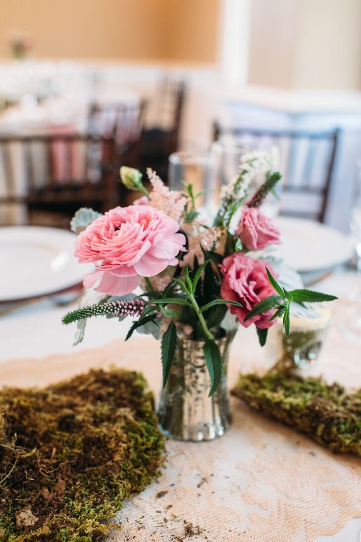 Of course, their pink wedding color also popped against the reception decor. Ibranyi Is Floral marked their tables with bunches of moss alongside mercury vases with pink ranunculus, astilbes, lisianthus and veronica. Wisps of added greenery and dusty miller broke up the display for a more natural look.