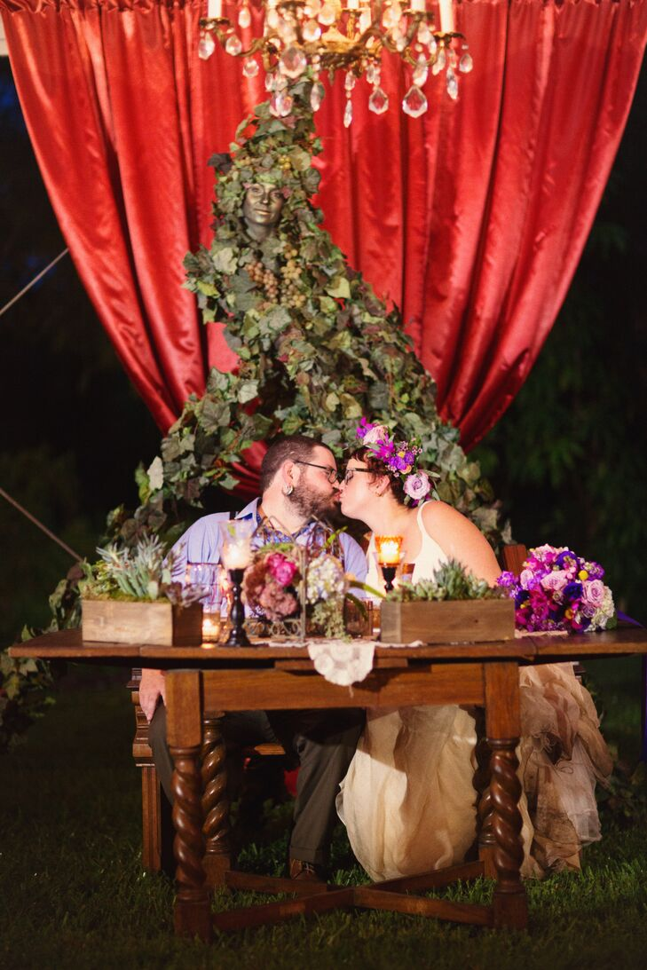 """Unlike the rest of the room, their sweetheart table had a more natural vibe with just a red curtain backdrop as their main burst of color. Each wooden breakaway vase along the front was overflowing with succulents and moss to fit the garden setting. Annie and Owen even set a """"living vine"""" performer behind them to enhance the natural atmosphere."""