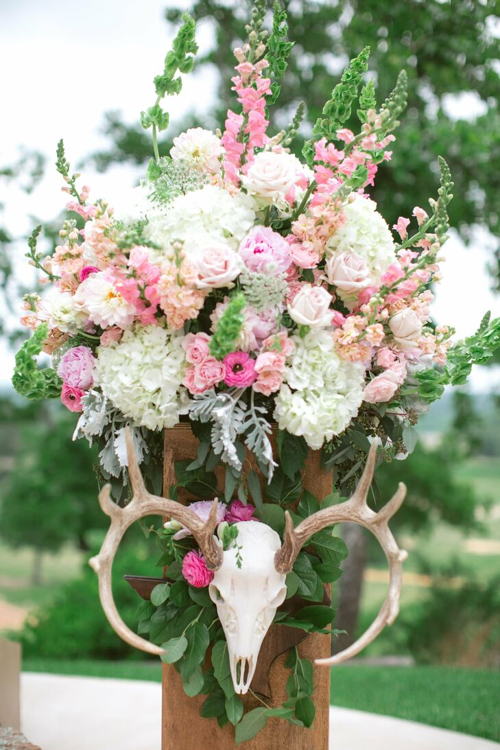 Arrangements of ivory, pink and peach blossoms decorated the pillars on either side of the ceremony altar. The finishing touch --- an deer skull placed on each to tie into the day's rustic, ranch theme.