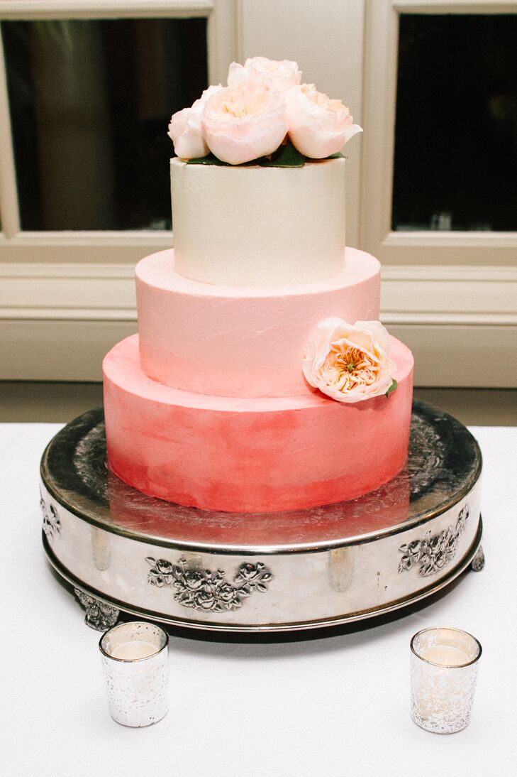 Pink ombre frosting on the couple's three-tier lemon wedding cake tied in with the day's vibrant color scheme. For a finishing touch, the cake was topped off with a fresh bunch of peach and white tea roses.