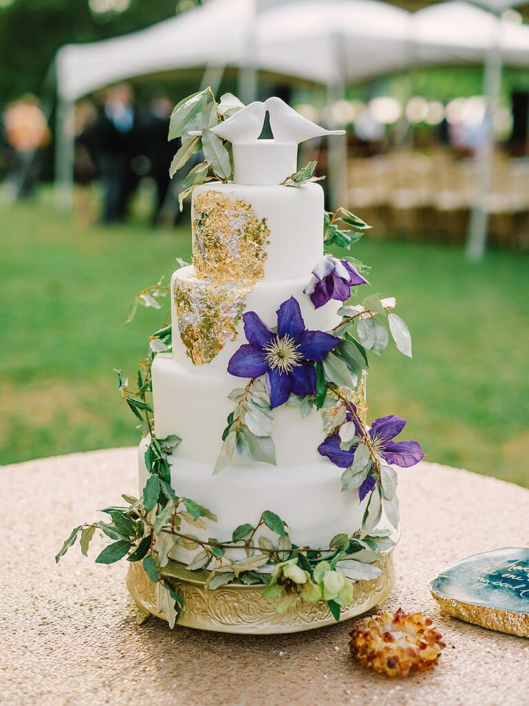 Romantic white wedding cake with gold foil and purple clematis