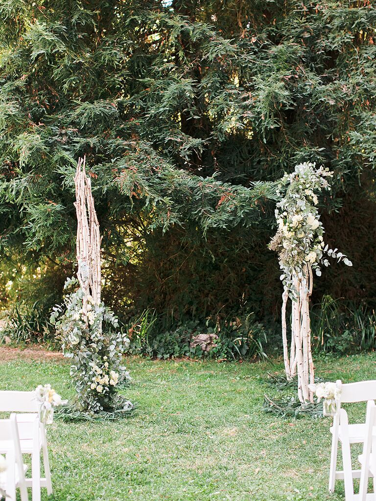 A simple, rustic wood and greenery arch for an outdoor wedding