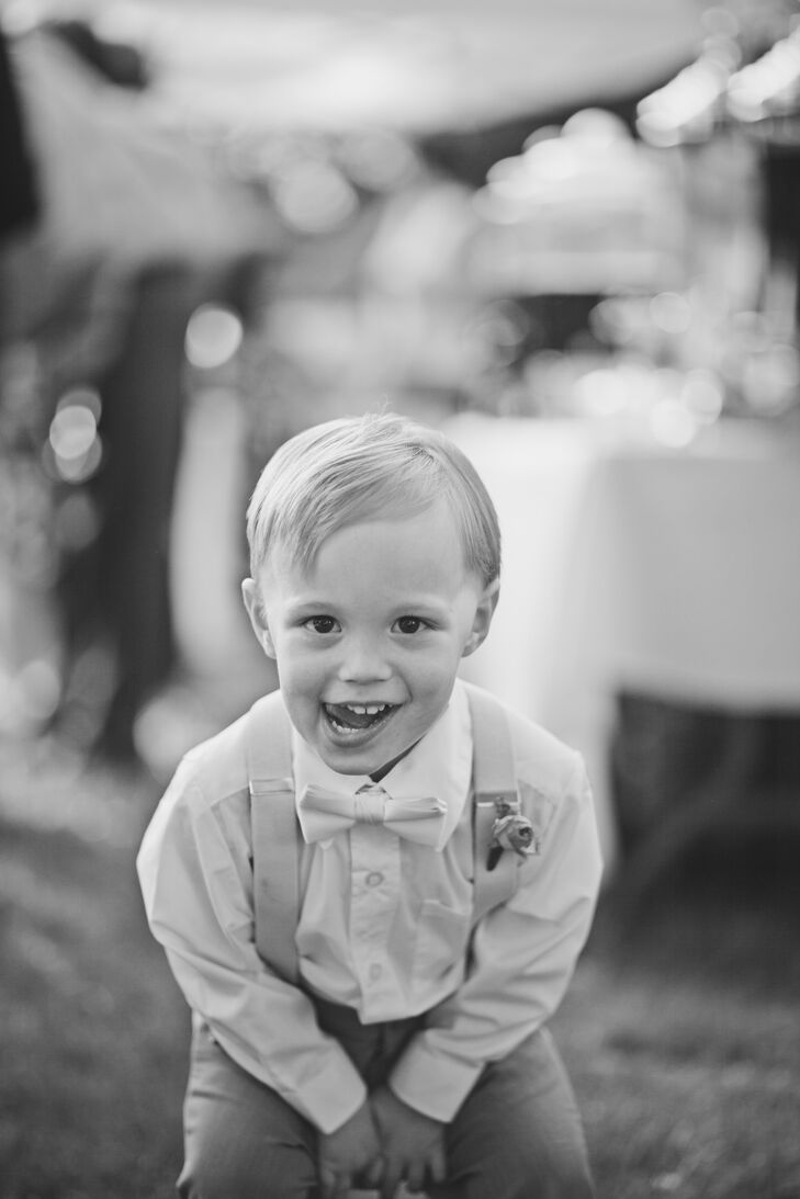 The ring bearer donned a white shirt, a white bow tie, suspenders and slacks. He even had a little rose boutonniere to complete his look. Although he was a little less formal than the groomsmen, who wore three-piece gray suits, he definitely matched the wedding's theme.
