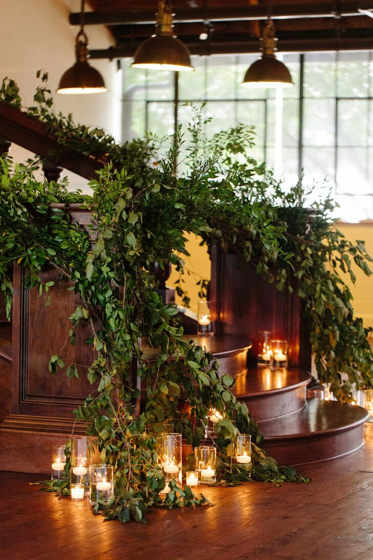 """""""I wanted to match the outdoor courtyard's greenery, so I asked our florist to try to emulate that on the staircase,"""" Deborah says. """"She did a beautiful job of keeping the shape and texture very natural and romanticizing it with votive candles."""""""
