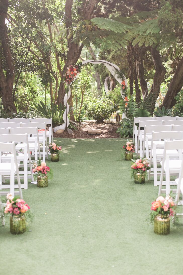 "Jillian and Adam exchanged vows in a secluded, shady part of the San Diego Botanic Garden in Encinitas, California. ""Since it was a garden space, we didn't need too many flowers, but we had gold vases with flowers and petals down the aisle, and we decorated the arch with fabric and more flowers,"" Jillian says."