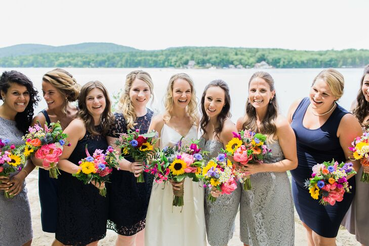 Liz's bridesmaids' gray and navy blue dresses provided the perfect backdrop for the bouquets, the soft neutral tones allowing the cheerful yellow, pink and purple blooms to pop. Liz let each choose her own style and color so they would all feel comfortable all night.