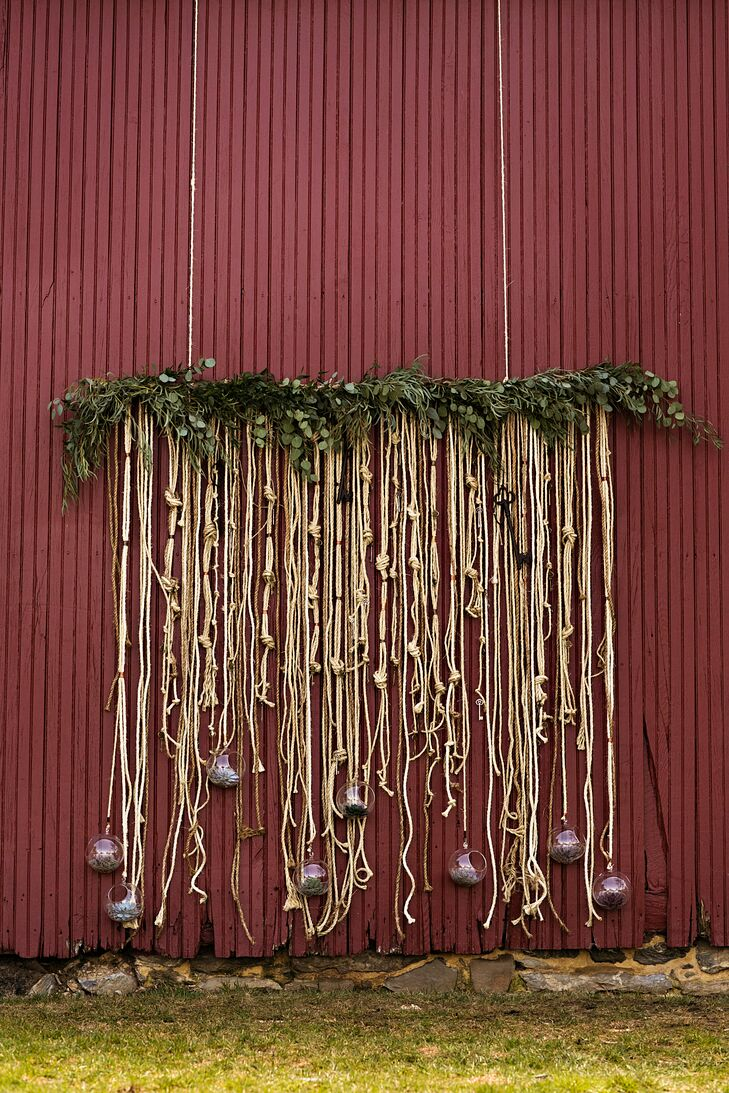 """""""Since we had been together for over 12 years, we pulled in the theme of finally tying the knot,"""" David says. Their custom ceremony backdrop reflected this to a T. The base of natural eucalyptus was connected to dozens of knotted gold rope. Each one had rustic, hanging succulents, keys and glass votives tied to the ends."""