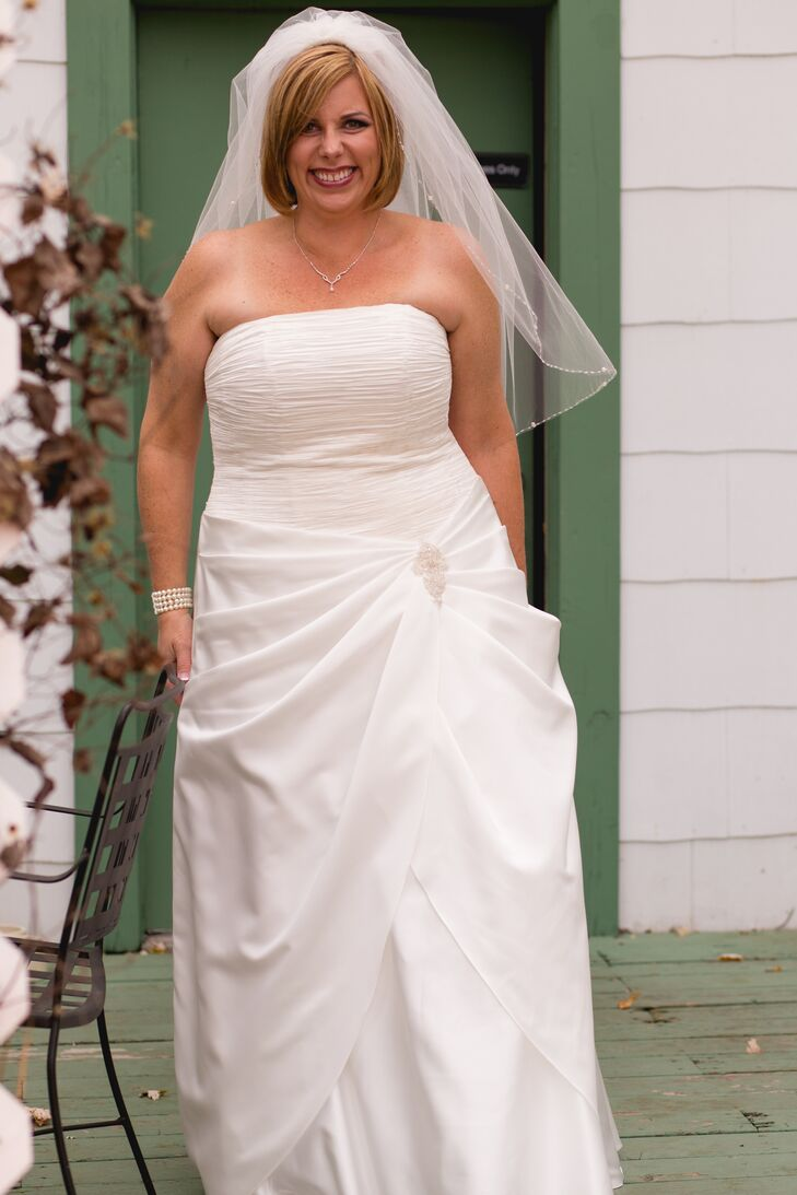 "Leslie had originally planned to wear a simple dress and a birdcage veil for the wedding to keep things more low-key. But, a trip to the bridal salon quickly changed her mind. She decided to try on a traditional floor-length gown in a strapless, A-line silhouette by David's Bridal. The gown featured elegant asymmetric draping and a crystal brooch for a bit of decorative flair. ""When I tried on this particular dress, my dear friend who went with me to try on dresses started crying. We then knew that this was the dress,"" says Leslie."