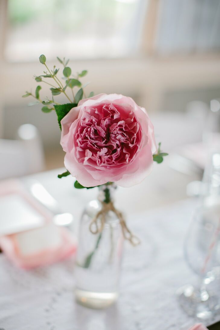 Pink garden roses were displayed in assorted glass vases along lace runners in the center of the farm tables.