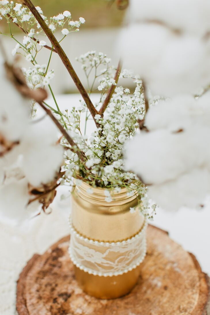 The bride and groom went for a simple, rustic vibe for their wedding, using cost-effective baby's-breath and cotton for their centerpieces in DIY gold painted mason jars wrapped in lace.