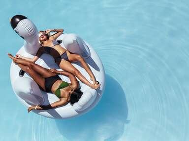 women floating on swan pool float