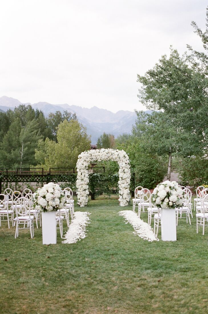 All-White Ceremony Decor With White Floral Arch