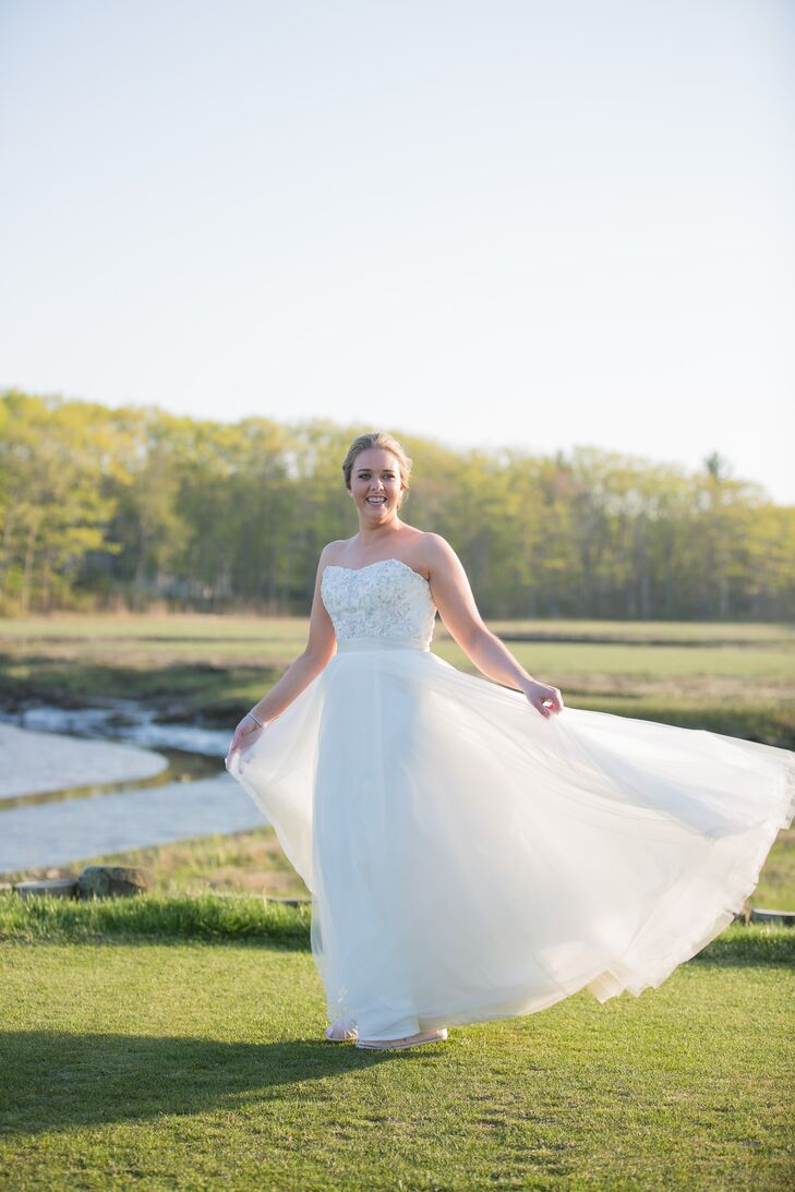 """To go with the wedding's seaside elegance theme, a """"princess dress"""" was a must for Amy. She visited Madeleine's Daughter in Portsmouth, New Hampshire, where she found an airy A-line Watters gown with a strapless embellished bodice and lightweight organza skirt. """"I wanted a dress with some beading and a manageable skirt and train,"""" Amy says. """"The Watters dress fit all my criteria. I originally didn't want to try it on, but it was the perfect dress for me."""""""