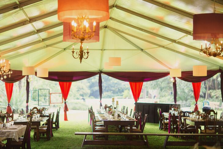 Unlike the white cocktail hour tent, their reception tent was filled with color. Everything from the chandelier shades to the curtains and the sashes along every other wooden reception chair included shades of red, orange, blue and purple.