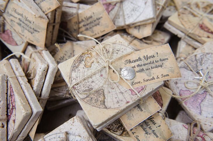 Sarah and Tom's travel theme did not stop at the seating chart. The couple sent all 196 guests home with globe-inspired coaster favors. Twine wrapped each one with a silver world-inspired charm and map-inspired thank-you note.