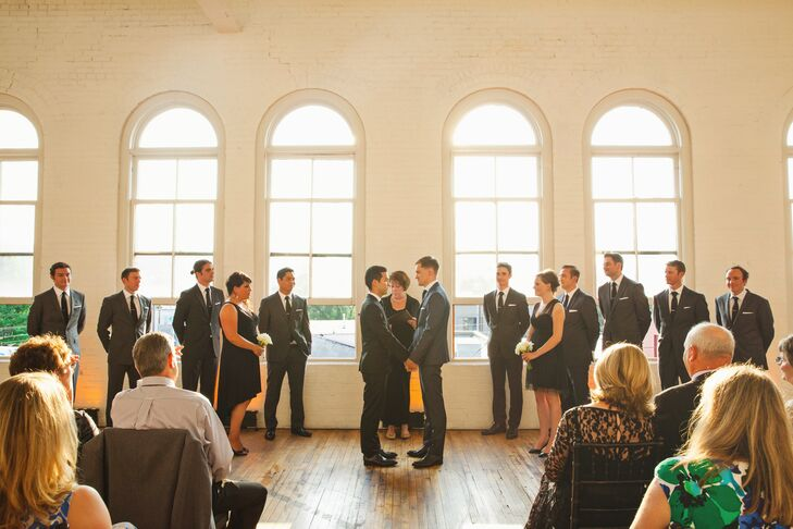 The grooms stood at the front of their altar with their officiant and wedding party during their wedding ceremony.