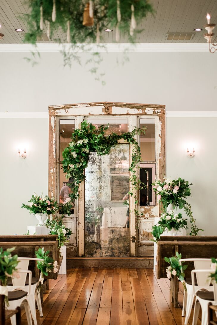 """""""The chapel was beautiful on its own with gorgeous chandeliers, rustic wooden floors and vintage pieces of furniture that added a lot of charm,"""" Mary says. To complement the chapel's charming decor, the couple added florals to the altar and draped greenery around a vintage mirror."""