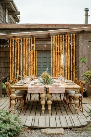 Backyard Wedding Reception With Wood Table and Marigold Garlands