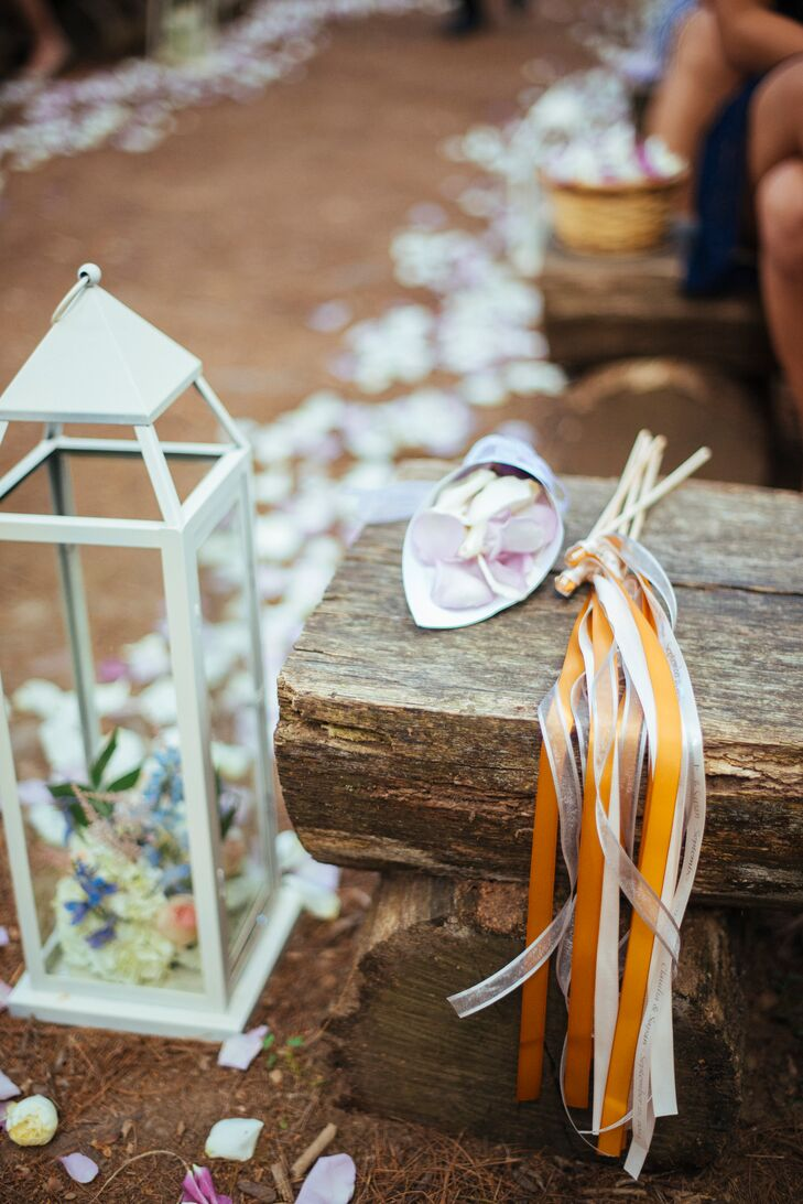 Guests were given small paper cups filled with rose petals to toss at the couple after the ceremony. White and orange ribbon streamers were also offered to guests to celebrate the couple.