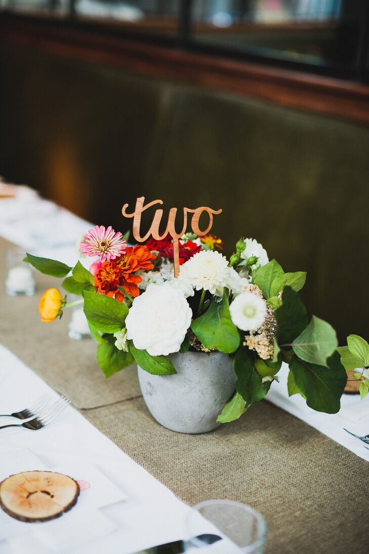 White and red flower arrangements in stone vases were positioned on table runners, with table numbers carved out of wood.