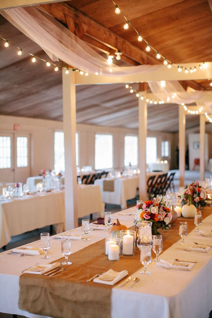String lights and white linens were draped across wood beams in the barn where the reception was held, creating an eye-catching visual effect.