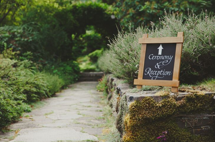 A chalkboard sign directed guests down a romantic, greenery-lined pathway toward the ceremony and reception site.