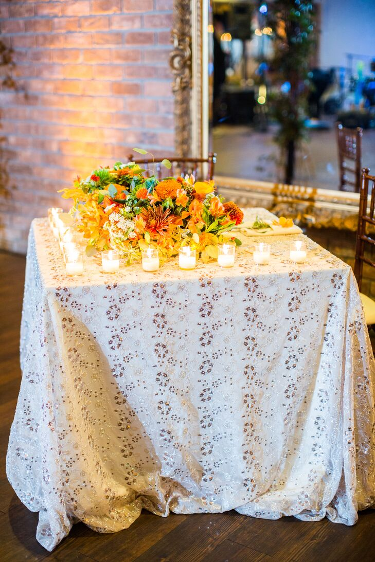Alison and Pierce's sweetheart table stood out from the rest. The square table had a textured champagne overlay with a pair of mahogany chiavari chairs. Gold votives lined the edge of the table, topped with a wild arrangement of orange blooms and greens.
